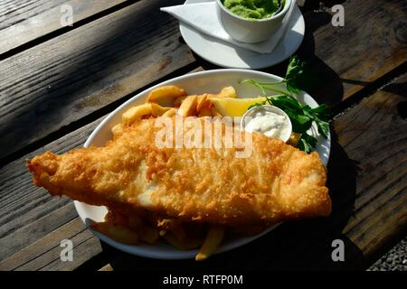 Fish and chips with mushy peas on an outside table The Shed Bistro Porthgain Pembrokeshire Wales Cymru UK GB - Stock Image