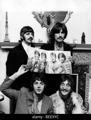 The Beatles (L-R) Ringo Starr, Paul McCartney, George Harrison, and John Lennon holding a photo of themselves from - Stock Image