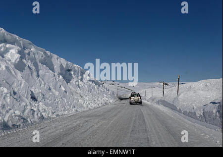 Car driving Eastbound on road E7 over Hardangervidda, Norway, with high walls of snow surrounding the road. - Stock Image