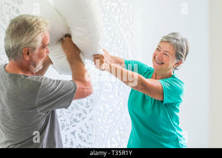 Pillows war at home for joke and to have fun together with senior mature caucasian couple playing in the bedroom - happiness and playful activity for  - Stock Image