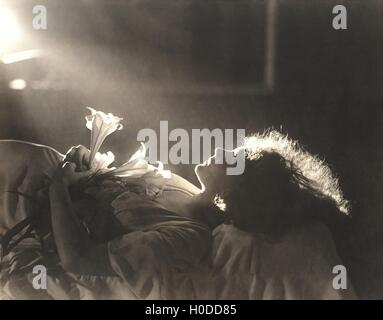 Sunlight falling on woman with flowers sleeping in bed - Stock Image