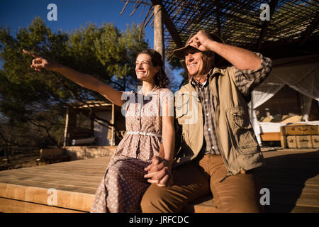 Couple sitting on wooden plank - Stock Image