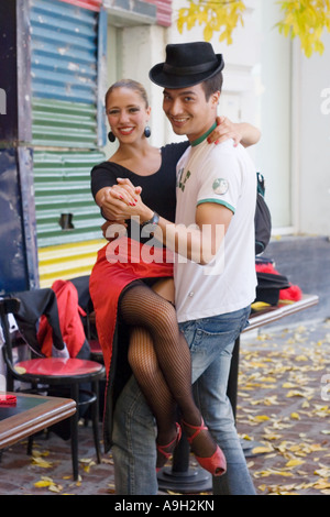 A tourist poses with a professional tango dance in Buenos Aires - Stock Image