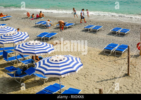 Tourists and families relax and play on the sandy Spiaggia di Fegina beach at the coastal city of Monterosso al Mare, on the northern coast of Italy. - Stock Image