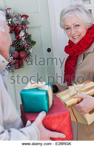 Couple with Christmas gifts standing at door - Stock Image