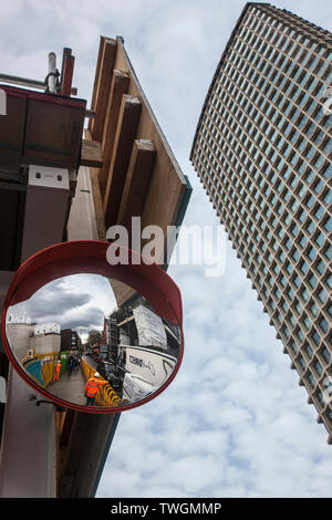 construction workers seen in convex mirror at tottenham court road crossrail works beside Centrepoint tower London, - Stock Image