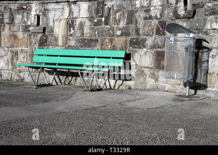 A green bench made of wood and trash can photographed on a sunny spring day in Nyon, Switzerland. In this photo you can also see asphalt walkway. - Stock Image
