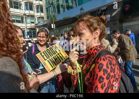 London, UK. 20th October 2018. A woman blows a whistle and anthother holds a Left Unity poster 'Europe Innit!'People gather with placards, banners and flags at Hyde Park Corner for the People's Vote March calling for a vote to give the final say on the Brexit deal or failure to get a deal. They say the new evidence which has come out since the referendum makes it essential to get a new mandate from the people to leave the EU. Peter Marshall/Alamy Live News - Stock Image