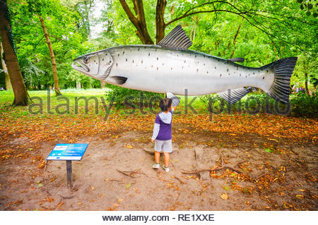 Kolobrzeg, Poland - August 10, 2018: Young boy standing in front of a large model salmon fish by a park - Stock Image