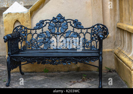 America, Charleston, South Carolina decorative black wrought iron bench in front of a church - Stock Image
