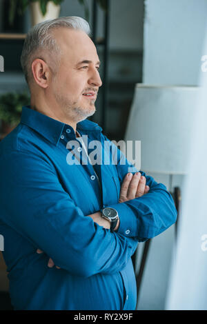 handsome man standing with crossed arms at home - Stock Image