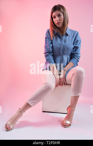 Attractive woman in blue jeans shirt and high heels on leg sitting on white cube stool and posing in studio and isolated on pink background - Stock Image