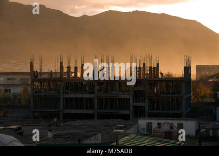 Construction workers framed by the setting sun with the Altai Mountains in the background on a hazy evening in Olgii, - Stock Image