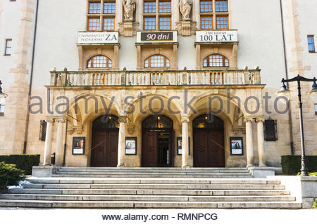 Poznan, Poland - February 6, 2019: Front entrance with three wooden doors of the Adam Mickiewicz university of economics building. Text on top window  - Stock Image