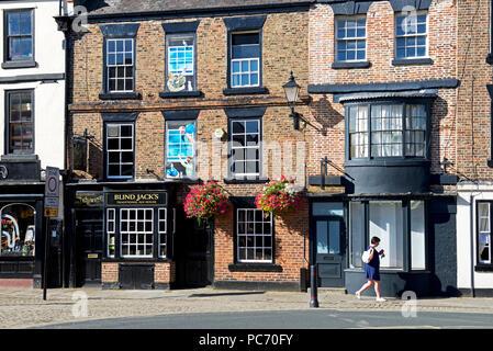 Woman walking past Blind Jack's pub, Knaresborough, North Yorkshire, England UK - Stock Image