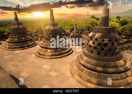 Sunset with the buddhist stupas at Borobudur temple, Indonesia - Stock Image