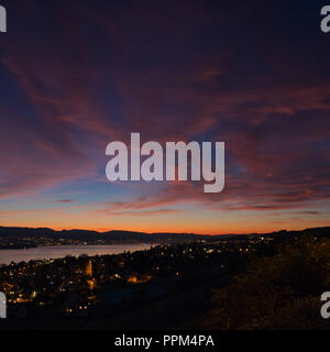 Lake with city with colorful sunset - Stock Image