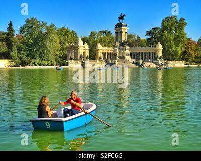 Two tourists paddle in a boat on the lake in Buen Retiro Park in Madrid, Spain. In the background is the Monument to Alfonso XII. Photo Credit - © COLIN HOSKINS. - Stock Image