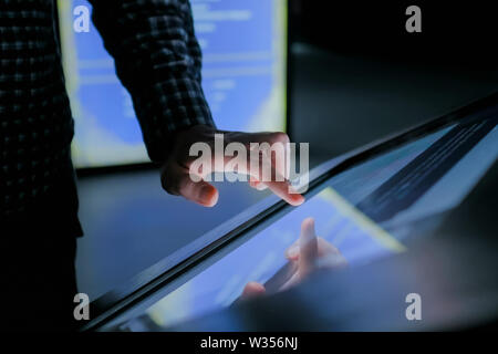 Man using interactive touchscreen display at modern history museum - Stock Image