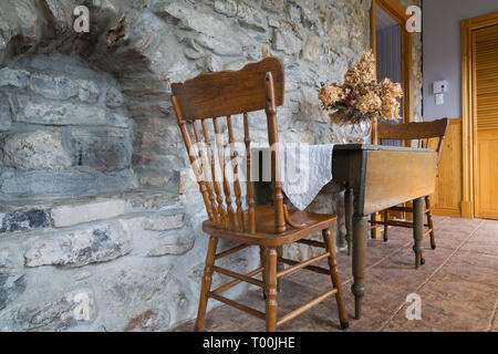 Antique wooden dining table and chairs in entryway with fieldstone wall and ceramic tile floor inside an old 1820 cottage style fieldstone house - Stock Image