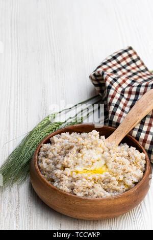 Barley  groats porridge in wooden bowl on white table - Stock Image