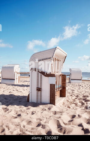Wicker beach chairs on empty sandy beach, color toning applied. - Stock Image