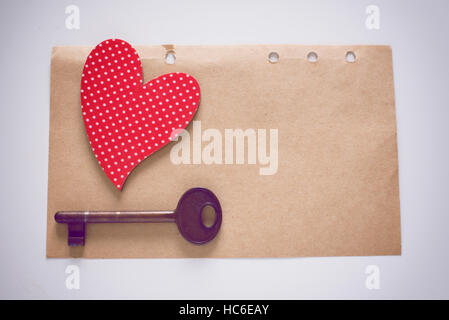 Red heart shape and antique key on old paper note - Stock Image