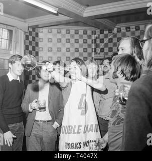 A young man drinking a Yard Of Ale in an English pour during the 1970s.A yard of ale or yard glass is a very tall beer glass used for drinking around 2 1⁄2 imperial pints (1.4 L) of beer, depending upon the diameter. The glass is approximately 1 yard (90 cm) long, shaped with a bulb at the bottom, and a widening shaft, which constitutes most of the height. The glass most likely originated in 17th-century England, where the glass was known also as a 'long glass', a 'Cambridge yard (glass)' and an 'ell glass'. It is associated by legend with stagecoach drivers. - Stock Image