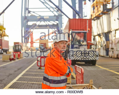 Dock worker awaiting crate being loaded to lorry waiting beside cargo ship - Stock Image