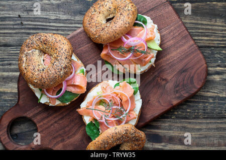 Lox - Everything bagel with smoked salmon, spinach, red onions, avocado and cream cheese over a rustic wood table background. Image shot from top view - Stock Image