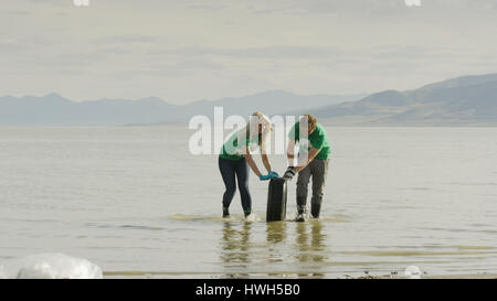 Environmental volunteers working together and cleaning tire debris pollution from scenic lake in remote landscape - Stock Image