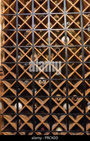 Wine bottles behind a metal security screen in the wine cellar of a house. - Stock Image