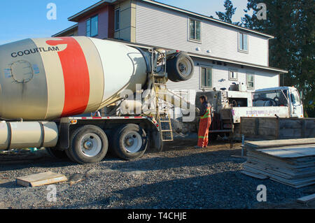 Cement truck with worker pouring cement outside new residential construction. - Stock Image