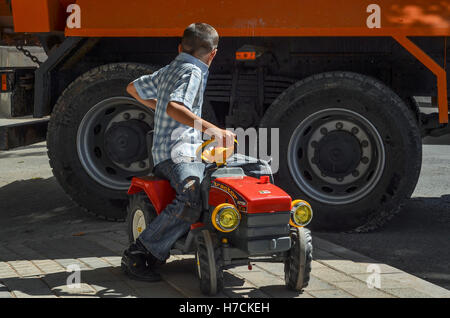 A boy plays with a toy tractor on a street in Istanbul. - Stock Image