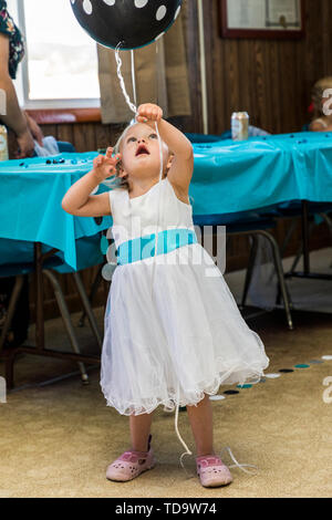 Child with helium filled balloons at wedding reception;  Congressional Church; Buena Vista; Colorado; USA - Stock Image