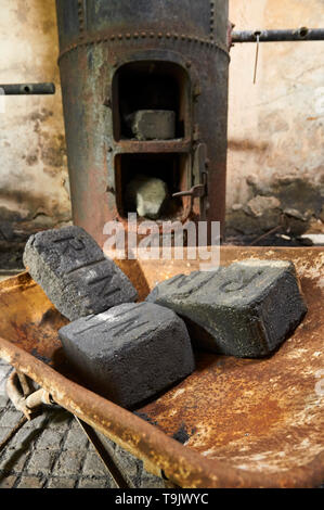 Old coal bricks in rusty wheelbarrow and old metal boilers at the Canfranc International railway station (Pyrenees, Huesca, Aragon, Spain) - Stock Image