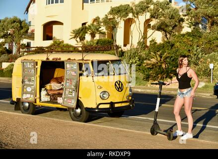 Attractive young woman hopping on Bird electric scooter next to classic Volkswagon VW minibus camper van parked at Sunset Cliffs, San Diego, USA - Stock Image