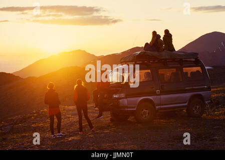 Group of friends sits on the mountain's top on background of mountains and sunset - Stock Image