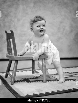 1920s BABY BOY STANDING HOLDING ON TO CHILD SIZE CHAIR - b2042 HAR001 HARS DISCOVERY SMILES JOYFUL BABY BOY GROWTH JUVENILES LOOKING  UP BLACK AND WHITE CAUCASIAN ETHNICITY CLOTH DIAPER HAR001 OLD FASHIONED - Stock Image