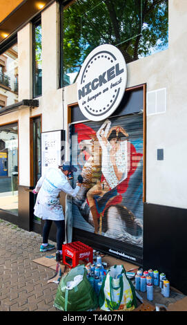 Woman mural artist painting a picture on a restaurant shutter in Seville - Stock Image
