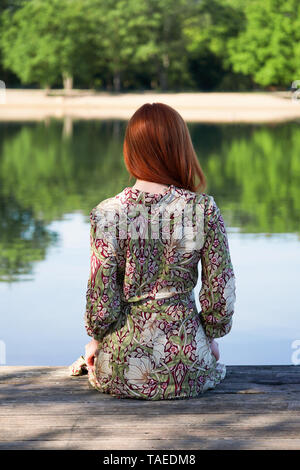 back view of young woman wearing summer dress and sitting on wooden pier looking at idyllic lake - Stock Image