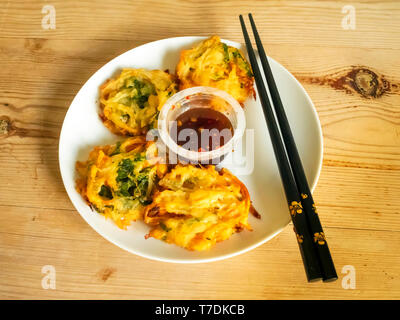 Japanese food Crispy Tempura Vegetable Fritters with Black Rice Vinegar Dip from M&S Food, on a white plate with black chopsticks - Stock Image