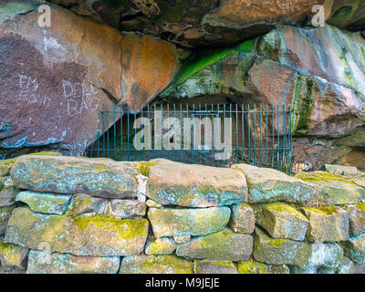 Cratcliffe Rocks, Derbyshire, UK. 26th Mar, 2018. New graffiti scratched into the rocks on the 14th century Hermit's Cave at the base of Cratcliffe Rocks, near the village of Elton, Derbyshire, within a four feet high stone carved Jesus Christ crucifixion on the wall, a niche for a lamp or candle, close to travellers on the Old Portway track Credit: Doug Blane/Alamy Live News - Stock Image