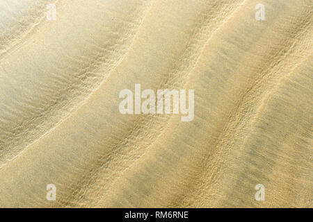 Full frame image of a wavy beach sand in a daylight, for background, wallpaper and backdrop - Stock Image