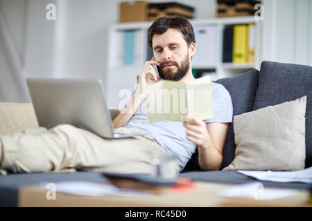Contemporary home office manager phoning clients while reading paper in front of laptop while lying on sofa - Stock Image
