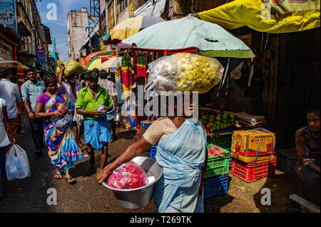 A market trader carries large amounts of food on their head in George Town market, Chennai, India - Stock Image