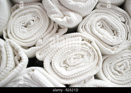 Loads of rolled white cotton bedspreads. Closeup - Stock Image