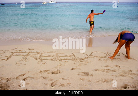 Couple playing on the beach in Formentera Spain - Stock Image