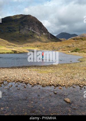 Lone female walker returning from Loch Coruisk crossing / fording river of Abhainn Camas Fhionnairigh at Camasunary Bay on Skye, Scotland, UK - Stock Image