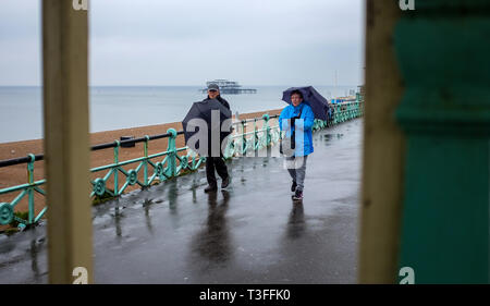 Brighton, UK. 09th Apr, 2019.  Umbrella weather on Brighton seafront today on a grey wet day along the south coast but the forecast is set to improve over the next few days throughout Britain Credit: Simon Dack/Alamy Live News - Stock Image